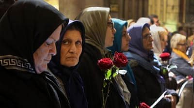 Muslim women hold red roses as they pray at the Notre Dame Cathedral during a memorial service for the victims of the Paris attacks [Maya Vidon-White/Al Jazeera]