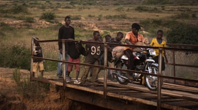 Children help a miner carry bags of mined tin over a bridge in Plateau State, Nigeria [Ali/Al Jazeera]