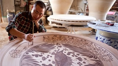 An artisan paints designs on a massive bowl in Jingdezhen, China.  Once the ceramics-making centre for emperors, today the city is the hub for replicas and forgeries [Al Jazeera]