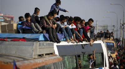 A severe fuel crisis has forced people in Nepal to travel on the roofs of buses [Navesh Chitrakar/Reuters]