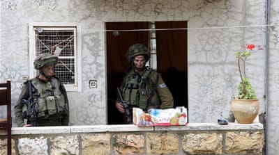 Israeli soldiers have occupied several Palestinian homes in Hebron and provided armed protection for settlers [EPA]