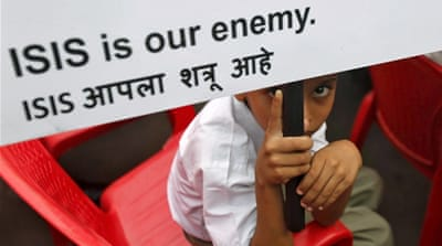 A Muslim boy looks on as he holds a placard at a rally organised by a Muslim charitable trust in Mumbai, India [REUTERS]