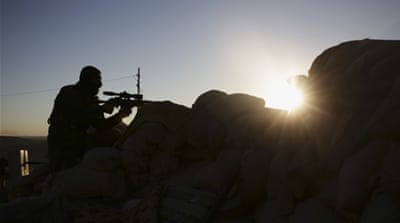 A Kurdish Peshmerga fighter stands guard in fighting against ISIL as the sun rises in Sinjar, Iraq [AP]