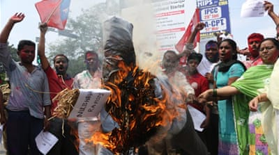 Activists burn an effigy representing rapists convicted in the 2012 bus attack on a woman [Mahesh Kumar A/Reuters]
