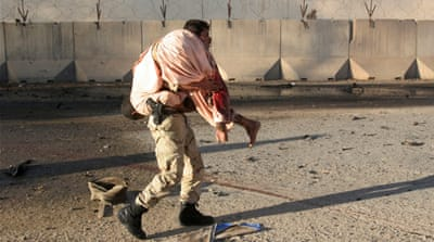 An Afghan soldier carries a wounded man after a suicide car bomb blast on a military convoy in Helmand [Abdul Malik/Reuters]