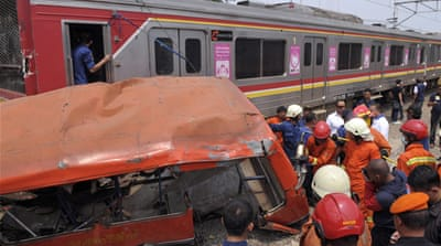 Rescuers remove the wreckage of a passenger minibus after it was hit by a commuter train in Jakarta [AP]