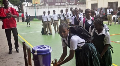 Liberian schoolchildren wash their hands before entering their classrooms as part of the Ebola prevention measures [AP]