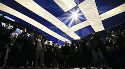 Protesters hold a giant Greek national flag during an anti-austerity demonstration in front of the parliament in Athens [Reuters]