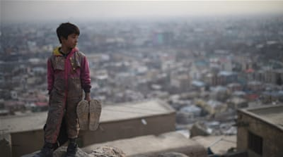 Afghan shoe-shine boy looks on from a hillside as he waits for customers in Kabul [AFP]