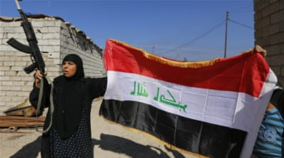 A woman with a weapon and the Iraqi flag in the town of al-Alam [Reuters]