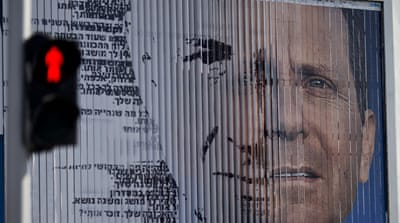 An election campaign billboard shifts between images of Herzog and Netanyahu [AP]
