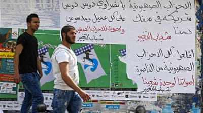 Arab Israeli men pass posters calling on Arabs not to vote for the Zionist parties [EPA]