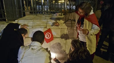 Tunisians holding candles pray at the entrance gate of the National Bardo Museum [AP]