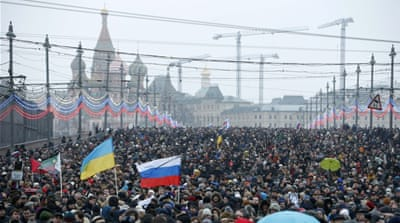 People hold Ukrainian and Russian national flags during a march to commemorate Kremlin critic Boris Nemtsov [REUTERS]