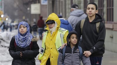 A crossing guard assists three Muslim school children at the end of a school day in the Brooklyn borough of New York [AP]