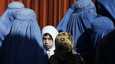 Afghan women lining up to receive winter relief assistance by the UNHCR in Kabul [Reuters]