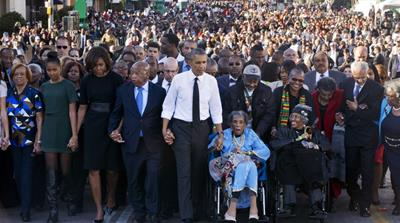 Obama walks as he holds hands with Amelia Boynton Robinson, who was beaten during 'Bloody Sunday' [AP]