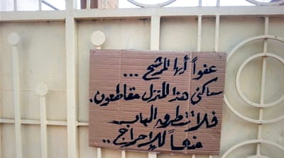 A sign in Arabic outside a Khartoum home says 'Dear candidate, don't bother knocking. This family is boycotting the elections' [Fatma Naib/Al Jazeera]