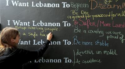 A Lebanese student writes on a wall during an event to mark the 40th anniversary of Lebanon's civil war [REUTERS]