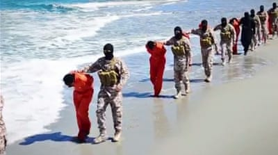 Video released online shows a group of about 12 men being beheaded, and another group of 16 men shot to death [AP]