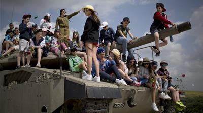 School children listen to an Israeli soldier speaking about Israel's wars on Memorial Day [AP]