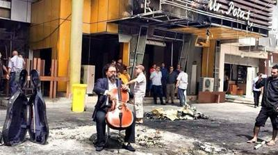 Karim Wasfi began to play his cello at the blast site in an act of defiance that has gone viral on the internet [Amal al-Jabouri]
