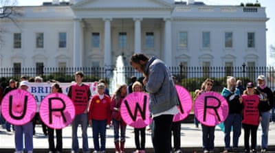 A Muslim man prays as anti-war protesters demonstrate in front of the White House in Washington, DC [Getty]