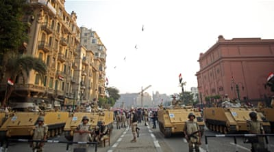Egyptian military helicopters fly overhead as army soldiers stand guard at an entrance to Tahrir Square, in Cairo, Egypt [AP]