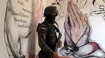A militarised policeman takes part in the repression of youth gangs in Honduras [AFP]