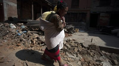 A Nepalese earthquake survivor carries her belongings a day after a major earthquake [EPA]