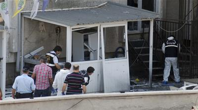 Police officers examine the site of the explosion at the HDP office in Mersin [Reuters]