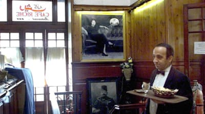 An Egyptian waiter walks in front of a picture of Egyptian Diva Umm Kalthoum at the historical Cafe Riche [AFP]