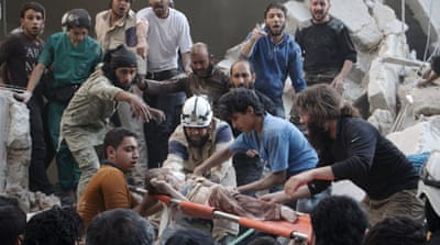 Syrian rescue workers and citizens carry a child on a stretcher after a reported barrel bomb attack in Aleppo [AFP]