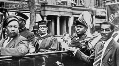 Marcus Garvey sits in the back of a car in a parade through Harlem circa 1920 in New York City [Getty]