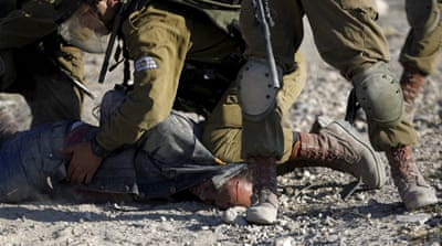 The video shows Israeli soldiers punching and kneeing the unarmed man in the head [Reuters]