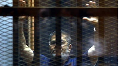 Former president Mohamed Morsi appeared inside a cage in the courtroom where he stood trial in Cairo [EPA]