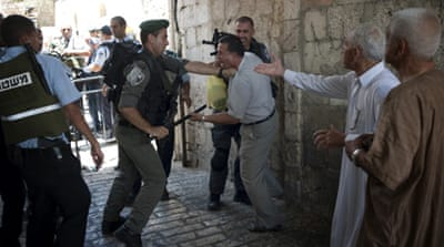 An Israeli border patrol policeman beats a Palestinian man with a truncheon close to an entrance of Al-Aqsa Mosque in 2014 [Getty]