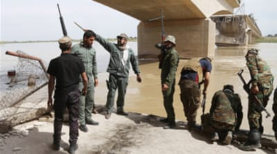 Iraqi security forces and militiamen on the bank of the Tigris River [AP]