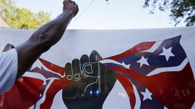 Demonstrators carry a flag showing a black fist closing around the confederate flag [REUTERS]