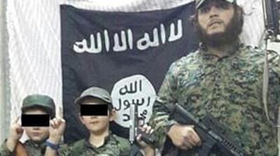 Australian man Khaled Sharrouf and his sons in front of an ISIL flag in Syria [Twitter]