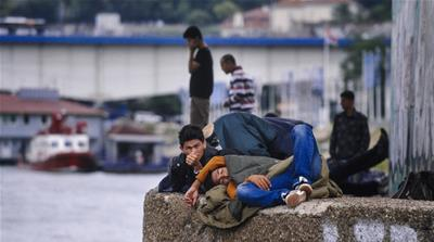 Migrants lying under a bridge on a bank of the river Sava in Belgrade, as they rest on their way to the Hungarian-Serbian border [AFP]