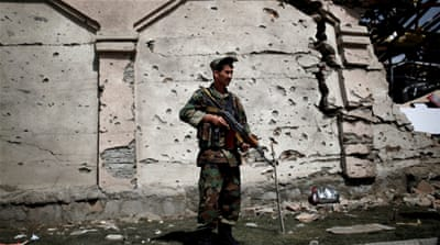A member of the Afghan security force in front of a damaged building a day after attacks outside the Afghan parliament [REUTERS]