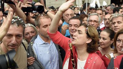 Ada Colau waves to the people as she crosses Sant Jaume square to meet Catalonia's regional president [AFP]