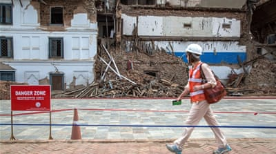 A delegate walks in front of a damaged palace ahead of the International Donors' Conference [Getty]