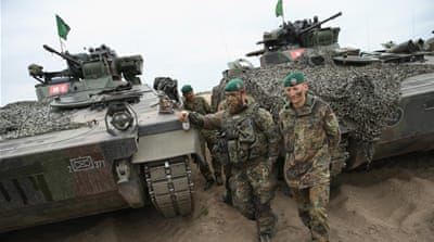 Soldiers stand next to their Marder light tanks during NATO military exercises [Getty]