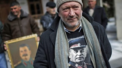 A supporter holds portraits of Soviet leaders Vladimir Lenin (left) and Josef Stalin in Moscow [Reuters]