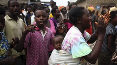 A protester dances as she carries her child in Bujumbura, Burundi [REUTERS]