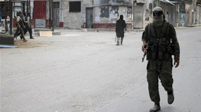 Members of the Nusra Front walk along a street in the northwestern city of Ariha in Idlib province [Reuters]