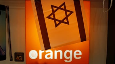 Israeli flags hang next to the logo of Orange mobile company in a store at a Jerusalem mall [REUTERS]