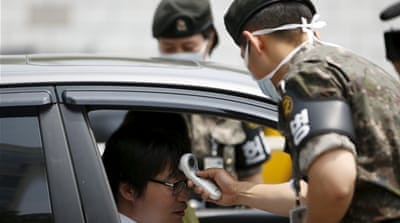 Soldiers check the body temperature of visitors at the defence ministry in Seoul in efforts to contain the outbreak [Reuters]